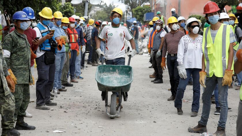 Volunteers work to remove rubble from the Neto supermarket where people were found dead in Mexico Ci