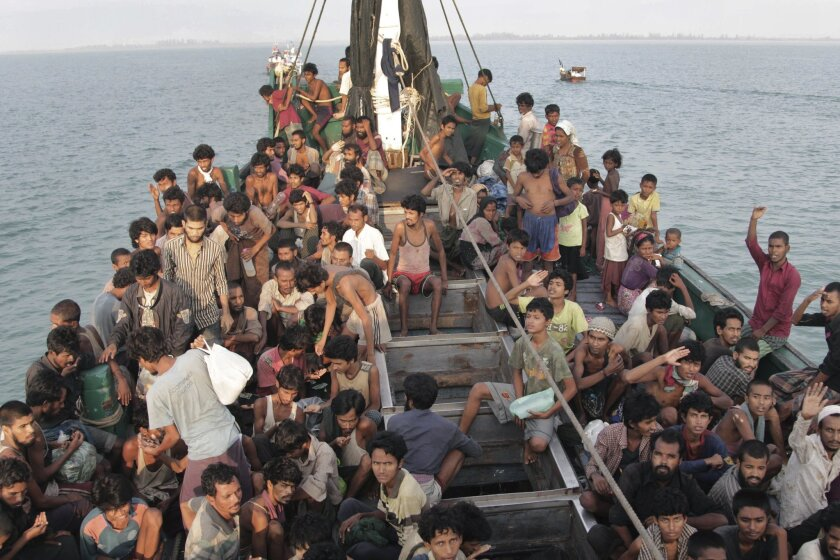 FILE - In this Wednesday, May 20, 2015 file photo, migrants wait to be be rescued by Acehnese fishermen on their boat on the sea off East Aceh, Indonesia. Many of the thousands of migrants abandoned at sea in Southeast Asia this month are Rohingya Muslims who fled their home country of Myanmar. The Rohingya are a Muslim minority in predominantly Buddhist Myanmar, also known as Burma. Numbering around 1.3 million, they are concentrated in western Rakhine state, which neighbors Bangladesh. (AP Photo/S. Yulinnas, File)