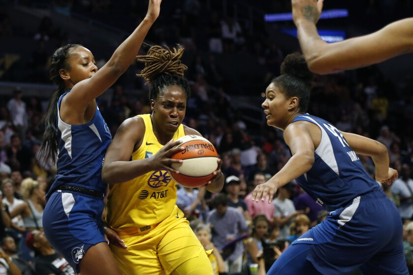 Sparks guard Chelsea Gray drives between the Lynx's Lexie Brown, right, and Damiris Dantas during a game last season.