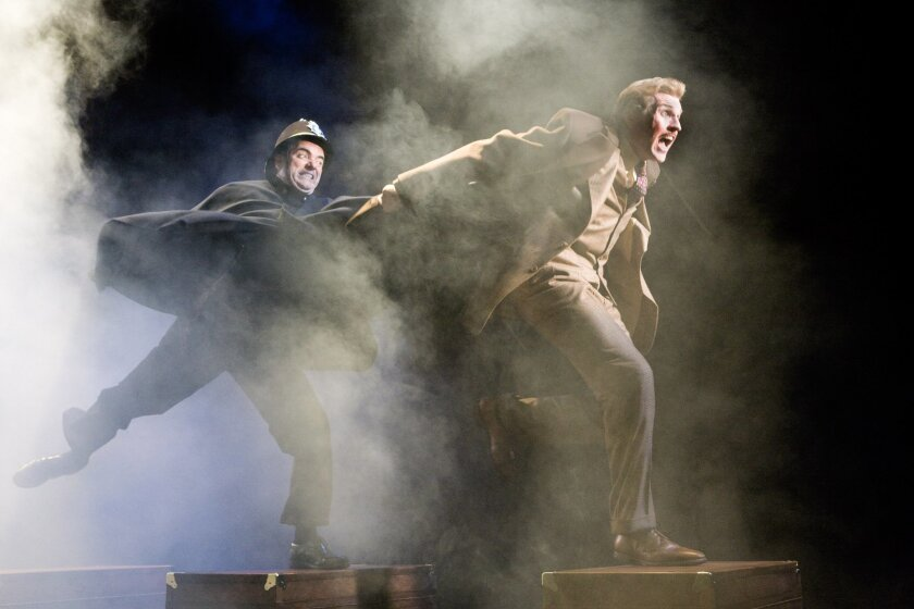 """A determined British cop (Eric Hissom, left) braves heavy stage fog to pursue the fugitive Richard Hannay (Ted Deasy) atop a makeshift train in the movie-inspired La Jolla Playhouse show """"Alfred Hitchcock's The 39 Steps."""" (Craig Schwartz)"""