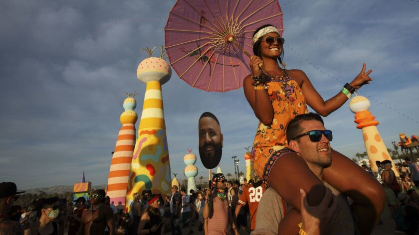 Marilou Stoltenberg, 33, of Hermosa Beach, holds an umbrella while riding on the shoulders of Justin Thompson, 37, of Long Beach, during weekend one of the Coachella Valley Music and Arts Festival at the Empire Polo Grounds Sunday, April 16, 2017, in Indio, Calif.