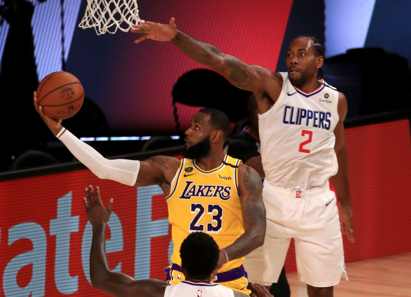 Lakers forward LeBron James, center, goes for a lay up against Clippers forward Kawhi Leonard.