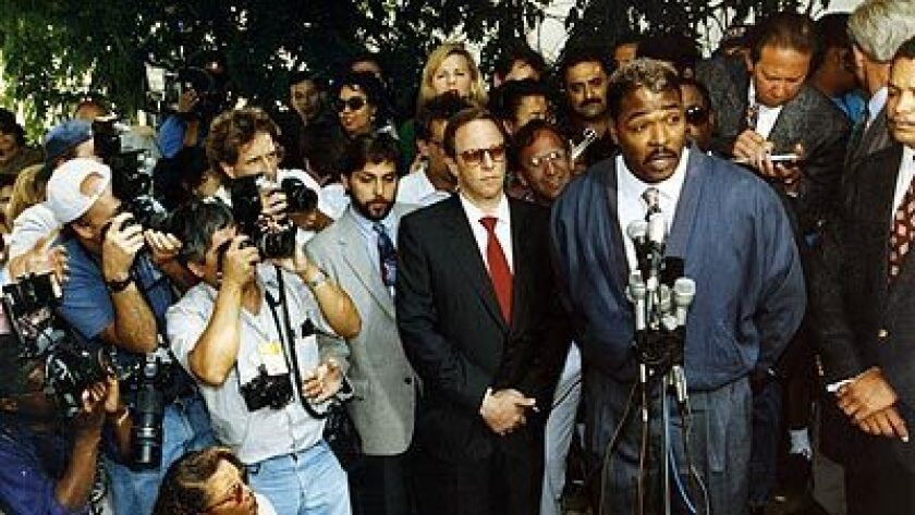 Rodney King, speaking to the media outside of his lawyer's office in Beverly Hills, with a gaggle of press behind him