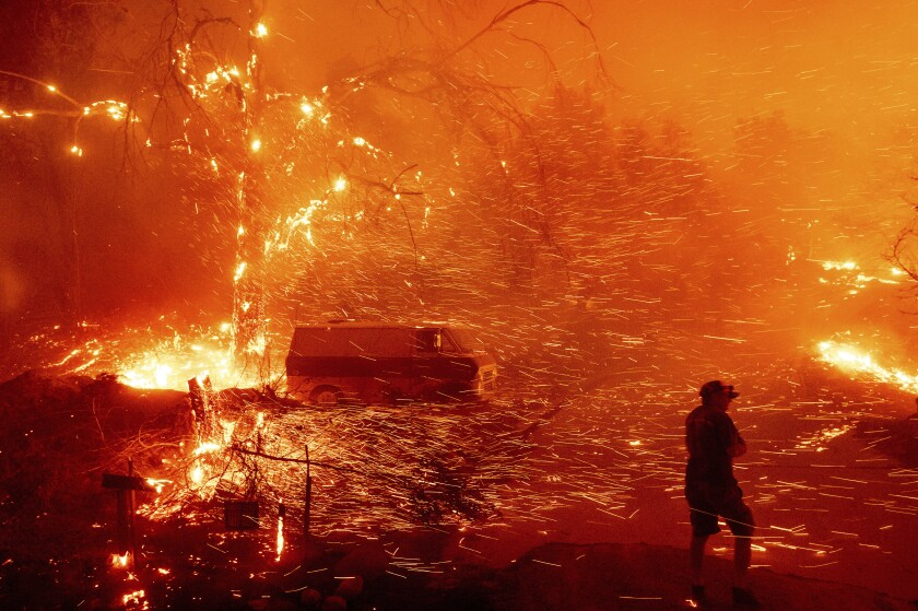 Bruce McDougal prepares to defend his home as the Bond Fire burns though the Silverado community in Orange County, Calif., on Thursday, Dec. 3, 2020. (AP Photo/Noah Berger)