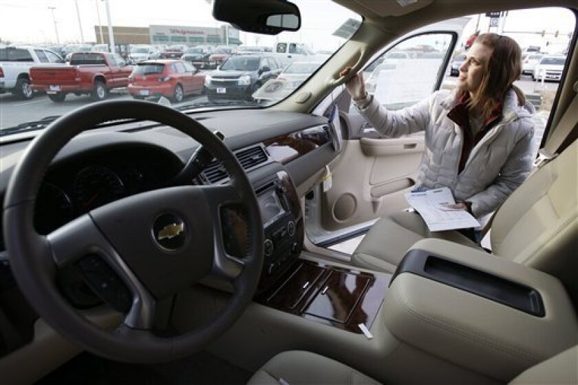 Katie Cummings, of Grinnell, Iowa, looks over a Chevrolet Tahoe that she and her husband were considering buying, Tuesday, Jan. 6, 2009, in Ankeny, Iowa. (AP Photo/Charlie Neibergall)