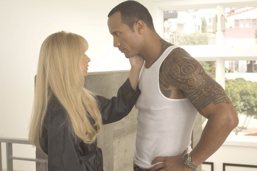 """Boxer Santaros (Dwayne """"The Rock"""" Johnson) and wife Madeline Frost Santaros (Mandy Moore) are linked to an influential politician."""