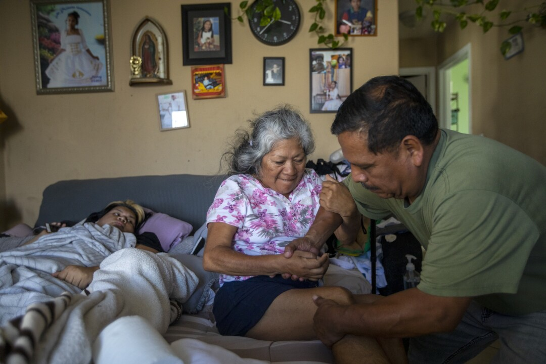 Jose Morales help his wife Reyna out of bed in South Los Angeles.