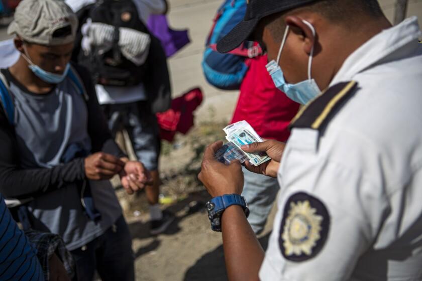 Un policía guatemalteco revisa las identificaciones de migrantes hondureños