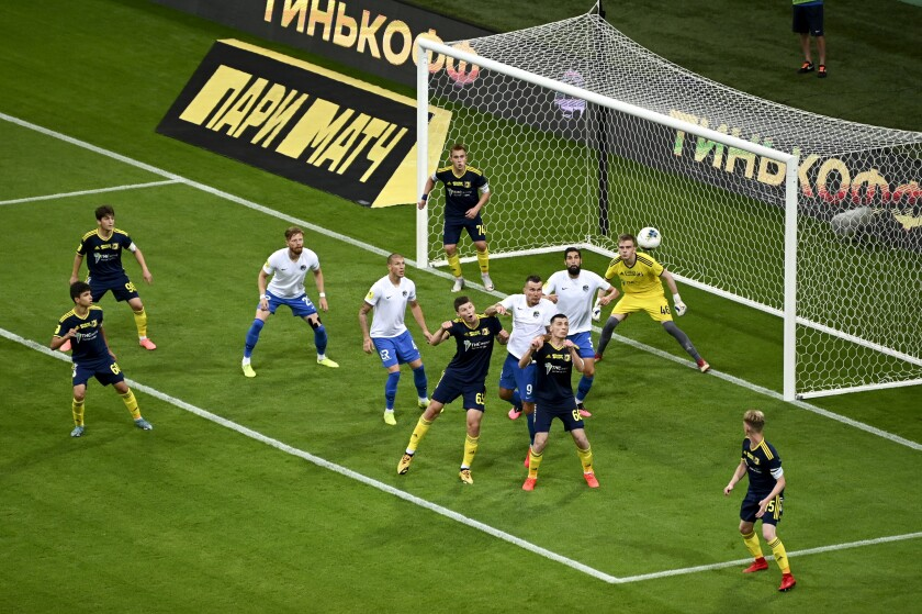 FC Sochi players, in white shirt, try to score against Rostov during a Russia Soccer Premier League soccer match against FC Rostov as the league was resumed after a three-month hiatus because of the coronavirus pandemic in Sochi, Russia, Friday, June 19, 2020. Rostov fielded a team of teenagers because its entire first-team squad is in isolation following a suspected outbreak of coronavirus. The match is being played with a minimum spectators to curb the spread of COVID-19. (AP Photo)