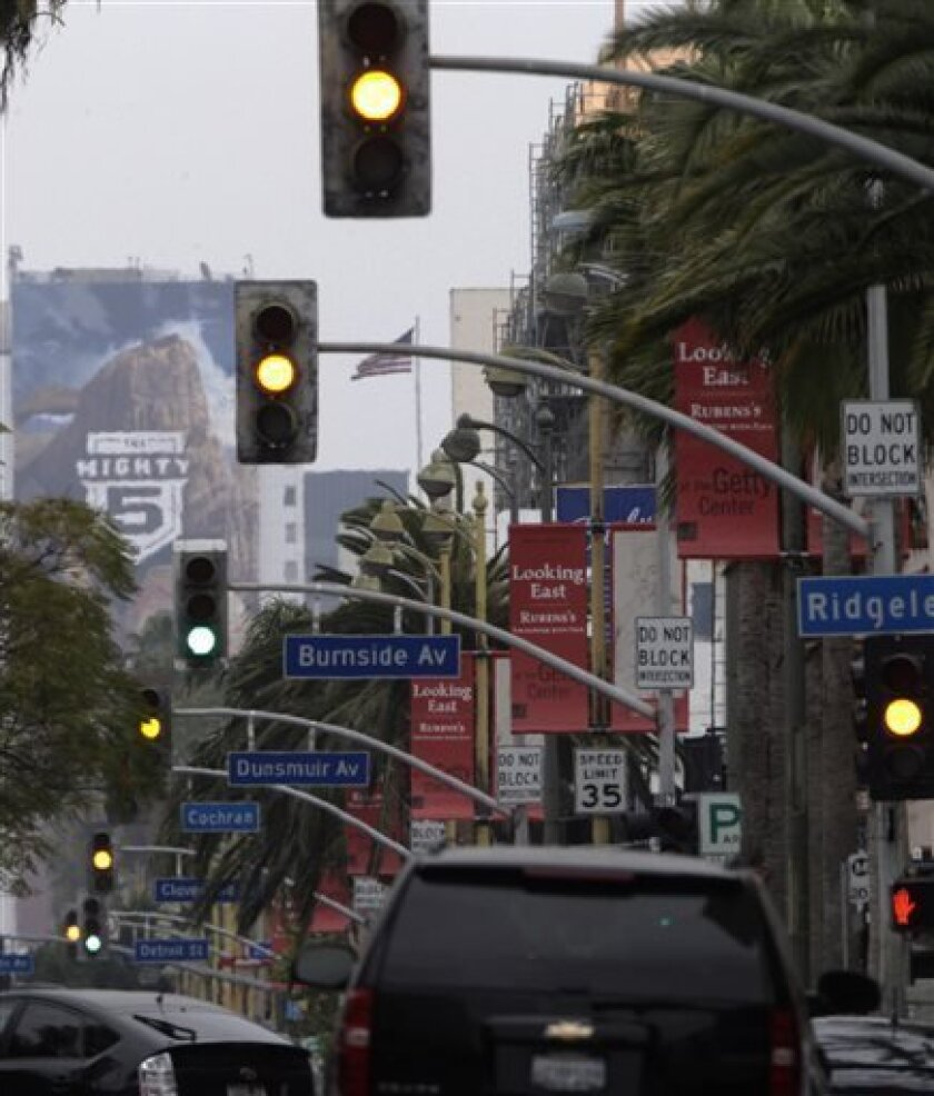 In this Wednesday, April 24, 2013 photo, traffic signals and vehicles are seen on Wilshire Boulevard in Los Angeles. The nation's most congested city has become a model for traffic control. With the flip of a switch in 2013, Los Angeles became a worldwide leader by synchronizing all of its nearly 4