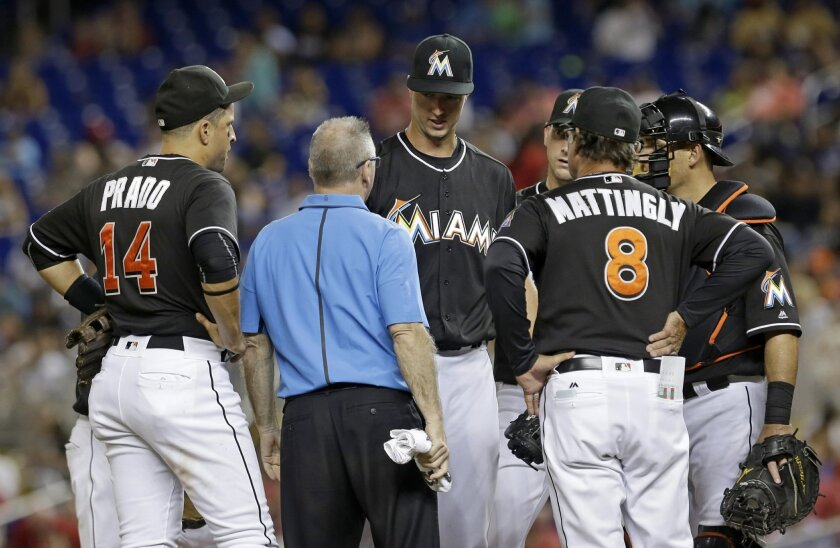 Miami Marlins' Colin Rea, third from left, talks manager Don Mattingly (8) in the fourth inning of a baseball game against the St. Louis Cardinals, Saturday, July 30, 2016, in Miami. Rea was relieved by David Phelps. Rea had an elbow injury in his Miami debut. The Marlins won 11-0. (AP Photo/Alan D