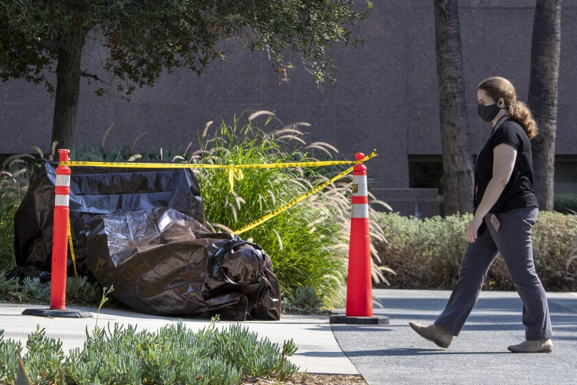 A vandalized statue is wrapped in a brown tarp in Grand Park Friday.