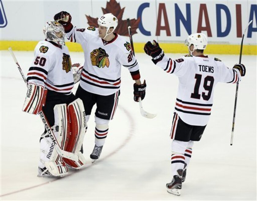 Chicago Blackhawks goalie Corey Crawford (50) is congratulated by left wing Bryan Bickell (29) and center Jonathan Toews (19) after defeating the Detroit Red Wings 2-1 in the shootout of an NHL hockey game, Sunday, March 3, 2013, in Detroit. Crawford made 33 saves in the game. (AP Photo/Duane Burleson)