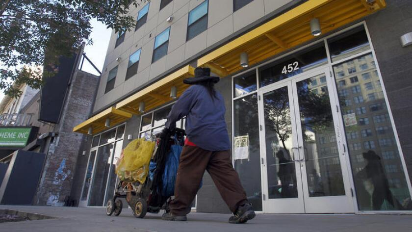 A homeless man pushes a cart in front of the New Genesis Apartments on skid row.