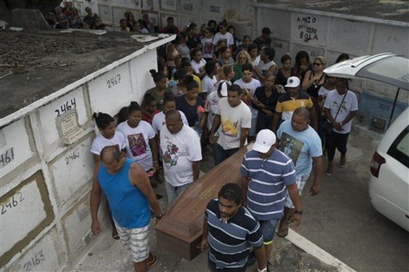 Familiares y amigos cargan el ataúd que contiene el cuerpo de Bruna Lace de Freitas _quien murió dos días antes víctima de una bala perdida cuando estaba dentro de su casa_ durante su funeral en Río de Janeiro, Brasil, el viernes 28 de octubre de 2016. (AP Foto/Leo Correa)