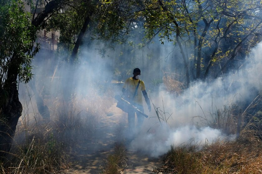 In this Feb. 12, 2016 photo, a municipal worker fumigates for the Aedes aegypti mosquito that transmits the Zika virus, in the Petare neighborhood of Caracas, Venezuela. Preventing the Zika virus' spread in the absence of a public campaign in a Venezuela where the health care system is near collapse means the people most at risk, the poor, don't even know about the epidemic. Chronic shortages have left the country without insect repellent or contraceptives, leaving women unable to guard against pregnancy, not to mention sexual transmission of the virus. (AP Photo/Fernando Llano)