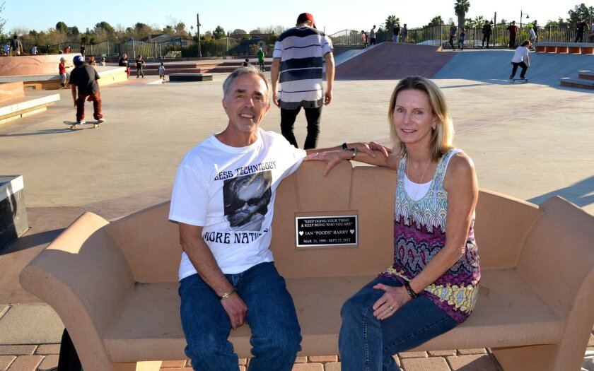 John and Alison Barry sit on a bench at the Encinitas Skate Plaza dedicated to their son Ian 'Poods' Barry, who passed away in 2012. Ian was known for his big heart, leading his parents to start a skateboarding nonprofit that aids underserved youth.