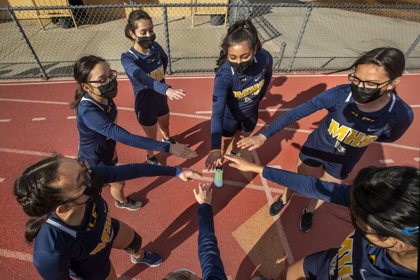Members of the Montebello High School girls cross country team are careful not to touch hands while wearing masks