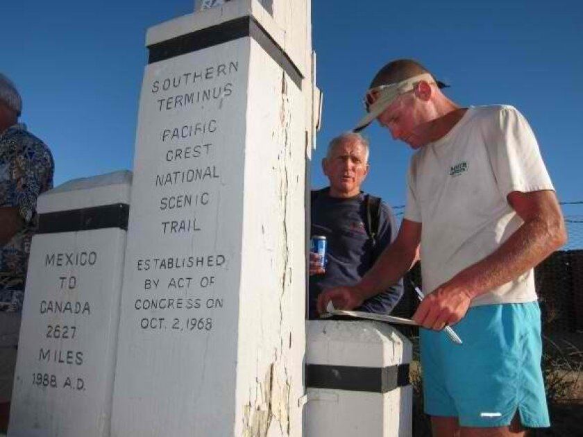 With former John Muir Trail speed record holder Reinhold Metzger looking on, long-distance hiker Scott Williamson, 39, of Truckee, signs in at the southern terminus of the Pacific Crest Trail to record his record unassisted time for the 2,627-mile hike.