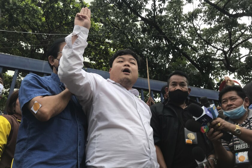 """Protest leader Parit """"Penguin"""" Chiwarak raises his hand with a three-fingered salute as a symbol of resistance outside the criminal court after he was released on bail Saturday, Aug. 15, 2020 in Bangkok, Thailand. Parit was arrested by police Friday on a sedition charge in connection with a July 18 protest. (AP Photo/Busaba Sivasomboon)"""