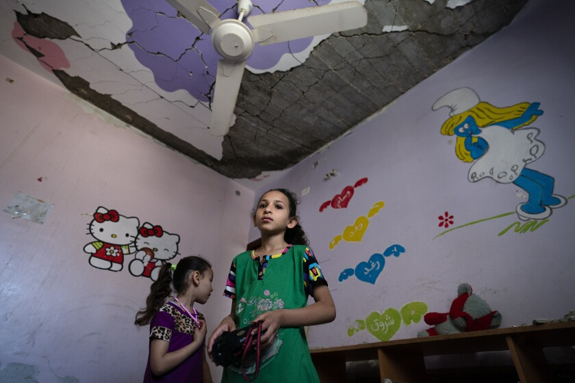 Suroq Al-Masri, 9, and her sister Razan, 4, stand for a portrait in their bedroom that was severely damaged when an airstrike destroyed a neighboring building prior to a cease-fire that halted an 11-day war between Gaza's Hamas rulers and Israel, Wednesday, May 26, 2021, in Beit Hanoun, Gaza Strip. (AP Photo/John Minchillo)