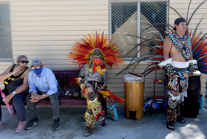 The participants of the march, including two dancers in traditional Aztec costume, rest in the shade on a bench in Ruben Salazar Park