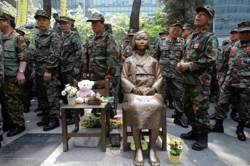 """South Korean Vietnam War veterans stand beside a statue honoring """"comfort women"""" during a rally in front of the Japanese Embassy in Seoul. Remarks by the mayor of Osaka on the historic perception of """"comfort women,"""" coerced into Japanese military brothels during World War II, have drawn intense criticism from neighboring countries and the United States."""