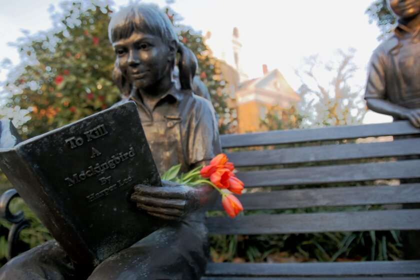 """Statue of a child reading """"To Kill a Mockingbird"""" in Harper Lee's hometown of Monroeville, Ala., was adorned with flowers following the author's death on Feb. 19."""