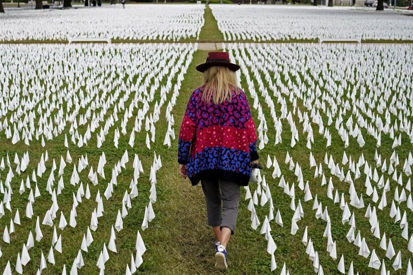 FILE - In this Oct. 27, 2020, Artist Suzanne Brennan Firstenberg walks among thousands of white flags planted in remembrance of Americans who have died of COVID-19 near Robert F. Kennedy Memorial Stadium in Washington. Regardless of the presidential election outcome, a vexing issue remains to be decided: Will the U.S. be able to tame a perilous pandemic that is surging as holidays, winter and other challenges approach? Public health experts fear the answer is no, at least in the short term, with potentially dire consequences. (AP Photo/Patrick Semansky, File)