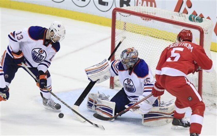 Edmonton Oilers goalie Nikolai Khabibulin (35), of Russia, pushes the puck toward teammate Cam Barker (13) after a shot by Detroit Red Wings defenseman Nicklas Lidstrom (5), of Sweden, during the second period of an NHL hockey game in Detroit, Wednesday, Feb. 8, 2012. (AP Photo/Carlos Osorio)