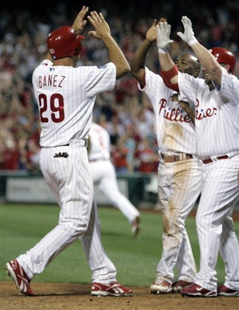 Philadelphia Phillies' Raul Ibanez is greeted at home plate by Jimmy Rollins, center, and Matt Stairs, right, after scoring the game-winning run on a single by Paul Bako in the ninth inning of a baseball game with the Pittsburgh Pirates, Saturday, July 11, 2009, in Philadelphia. The Phillies won 8-7. (AP Photo/Tom Mihalek)