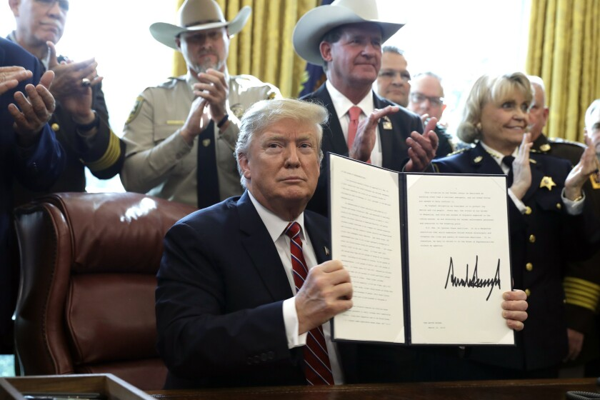 President Donald Trump holds up his first signed veto measure