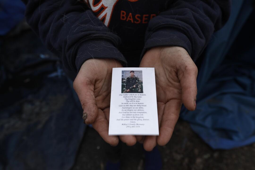 Melissa Millner holds a memorial card
