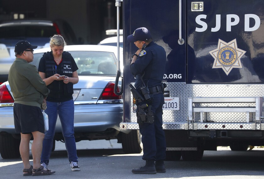 Members of the San Jose Police Department talk with an unidentified man, left, near the scene where