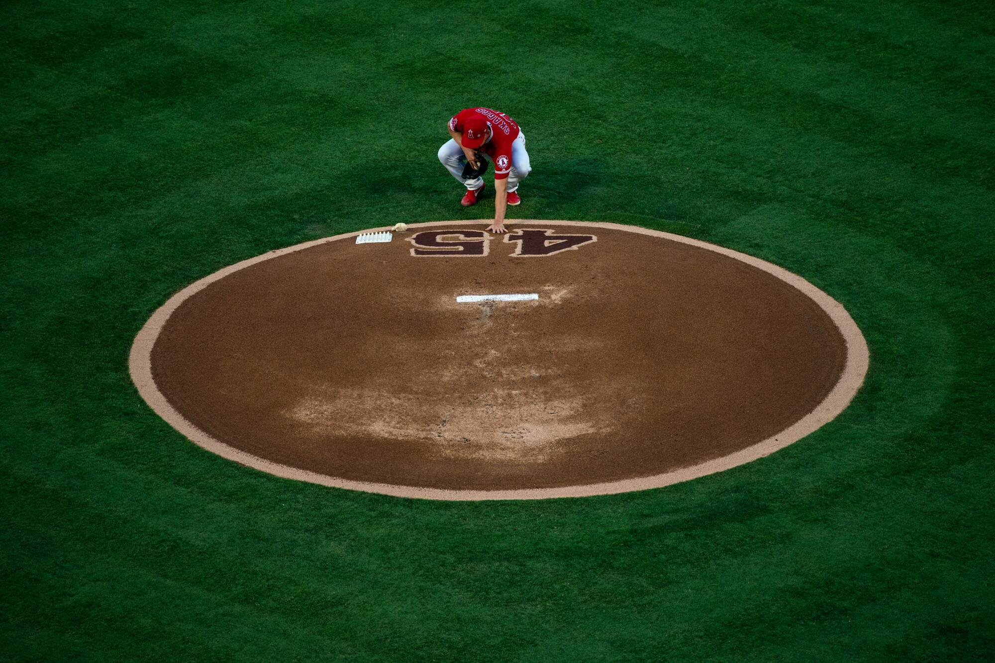 Los Angeles Angels starting pitcher Taylor Cole (67) places his hand on the No. 45 on the pitchers mound.