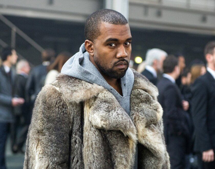 FILE - This Jan. 17, 2014 file photo shows singer Kanye West as he arrives for the Givenchy men's Fall-Winter 2014-2015 fashion collection in Paris.  West will not face criminal charges over an incident in which he apparently punched a man in a Beverly Hills chiropractor's office, prosecutors deter