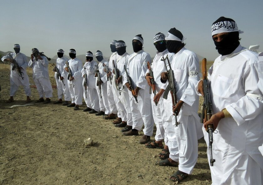 File, In this Aug. 15, 2016 photo, Taliban suicide bombers stand guard during a gathering of a breakaway Taliban faction, in the border area of Zabul province, Afghanistan. An Afghan official said, Wednesday, Sept. 8, 2016, that the Taliban have pushed into the capital of Uruzgan province in the country's south, triggering fierce clashes and prompting an evacuation of all government officials. The insurgent advance has left Afghan authorities only in charge of the city's police headquarters in Tirin Kot. The provincial spokesman, Doost Mohammad Nayab, says Taliban fighters are besieging the police headquarters and appealed on the government in Kabul for prompt reinforcements. (AP Photo/Mirwais Khan, File)