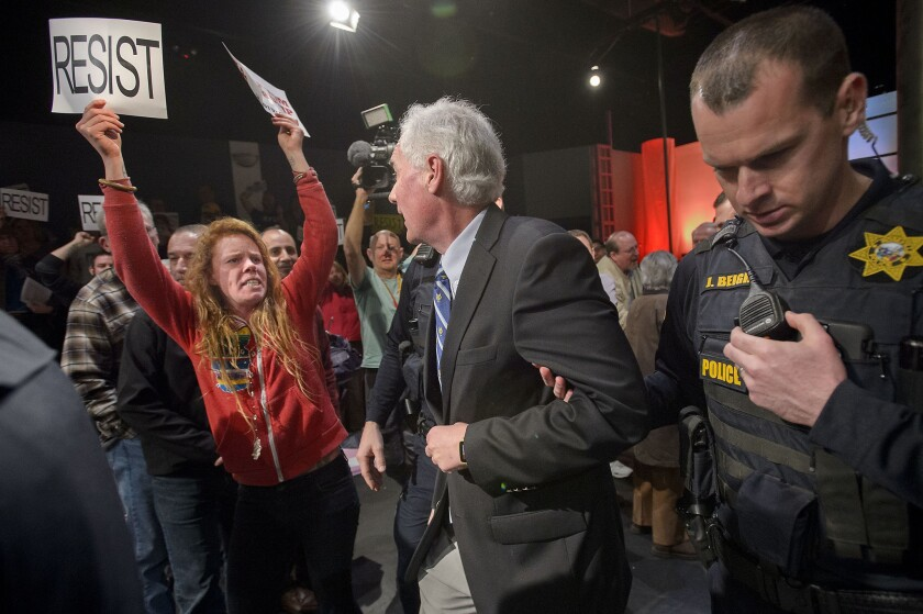 """Rep. Tom McClintock (R-Elk Grove) is escorted by police from a town hall meeting as protesters follow him, shouting, """"Shame on you!"""" (Randall Benton / Sacramento Bee)"""