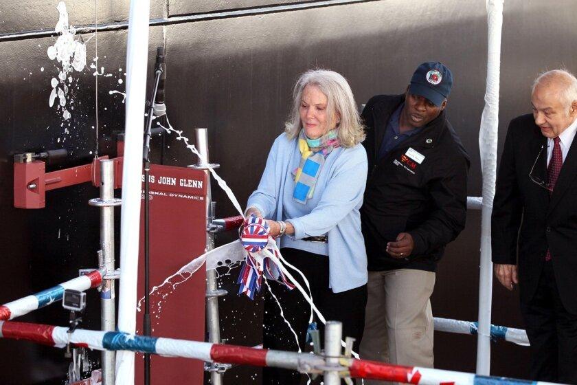 John Glenn's daughter Lyn Glenn smashes a bottle of champagne against the hull of the Mobile Landing Platform ship that bears her father's name.