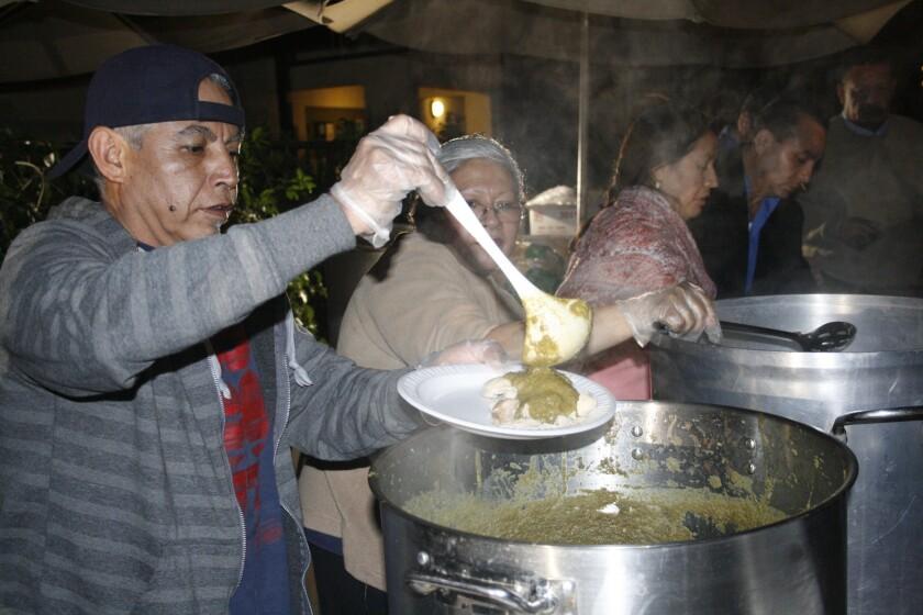Voluntarios sirven alimentos en la Misión Dolores durante la celebración del Thanksgiving.