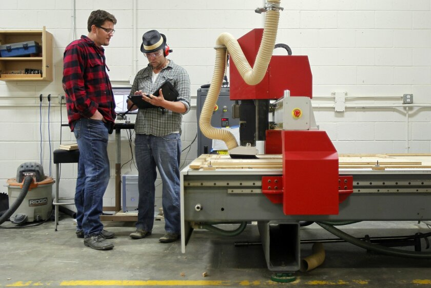 Michael Salmon, left, looks on as Devon Read uses a CNC router to cut pieces for a wood iPad cash register at MakerPlace. Salmon is one of the owners of the industrial workshop that is open to the public.
