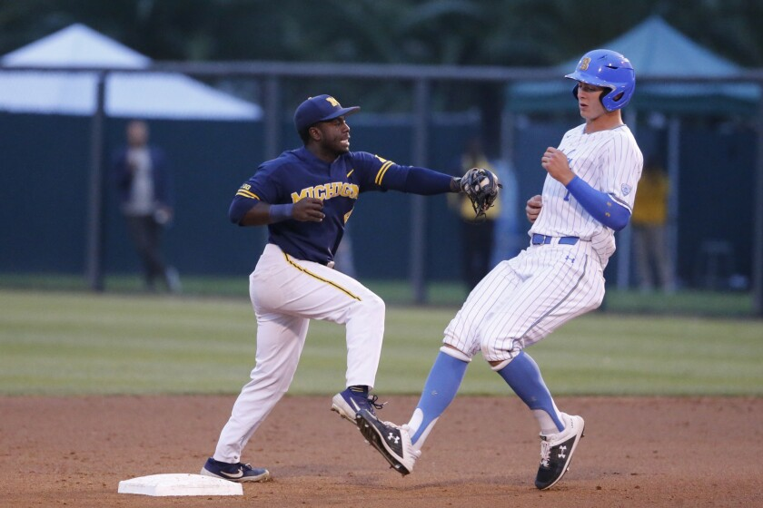 Michigan's Ako Thomas (4) tags out UCLA's Michael Toglia (7) on an attempted steal of second base du
