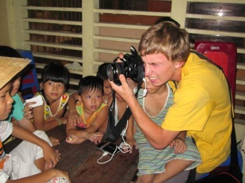 Daniel Galuppo, 18, a senior at Torrey Pines High School, taking pictures of orphans in Vietnam.