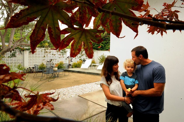 """Laura Haskell, Laird Stoneman and Andrew Stoneman stand under a Japanese maple at the front of their 1960 house. The couple created an elegantly spare courtyard in front of the 1,500 square-foot home using patterned cinder blocks. """"I liked the motif,"""" Haskell says of the blocks, though she adds that there aren't as many options as one might think."""