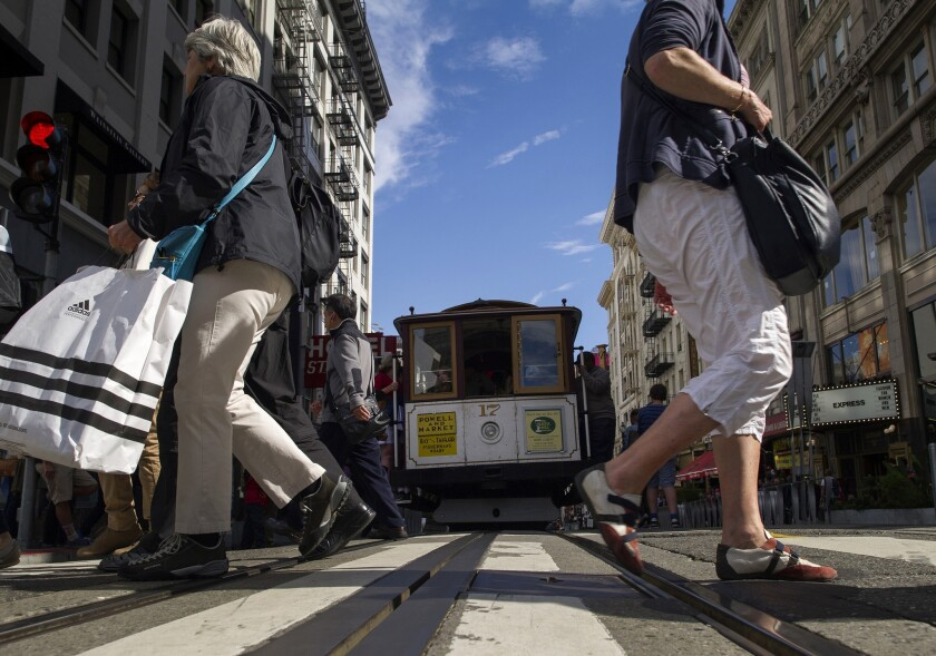 Pedestrians carry shopping bags while crossing in front of a cable car in San Francisco on July 7.