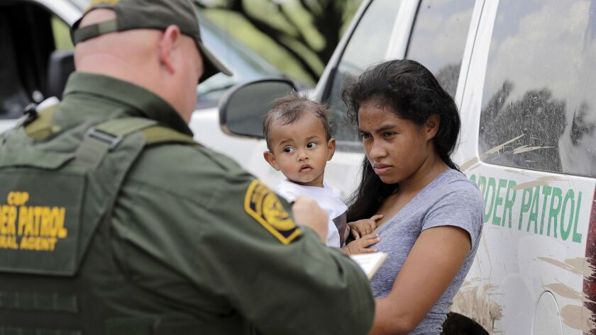 A mother from Honduras who illegally crossed the border near McAllen, Texas, with her 1-year-old child surrenders to U.S. Border Patrol agents in June.