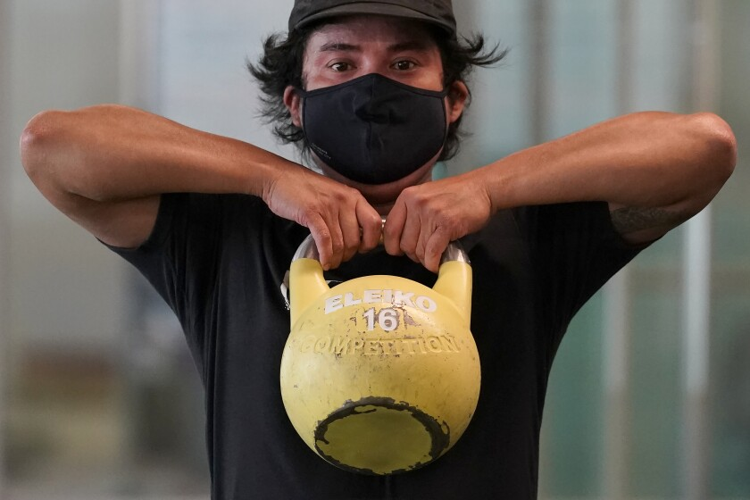Tim Robles wears a mask while lifting a kettlebell during a workout at Fitness SF Transbay gym.