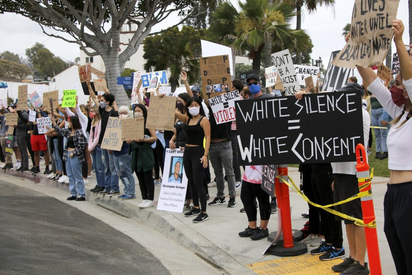 Dozens of Black Lives Matter protesters held signs and chanted at Main Beach Park in Laguna Beach on Friday.