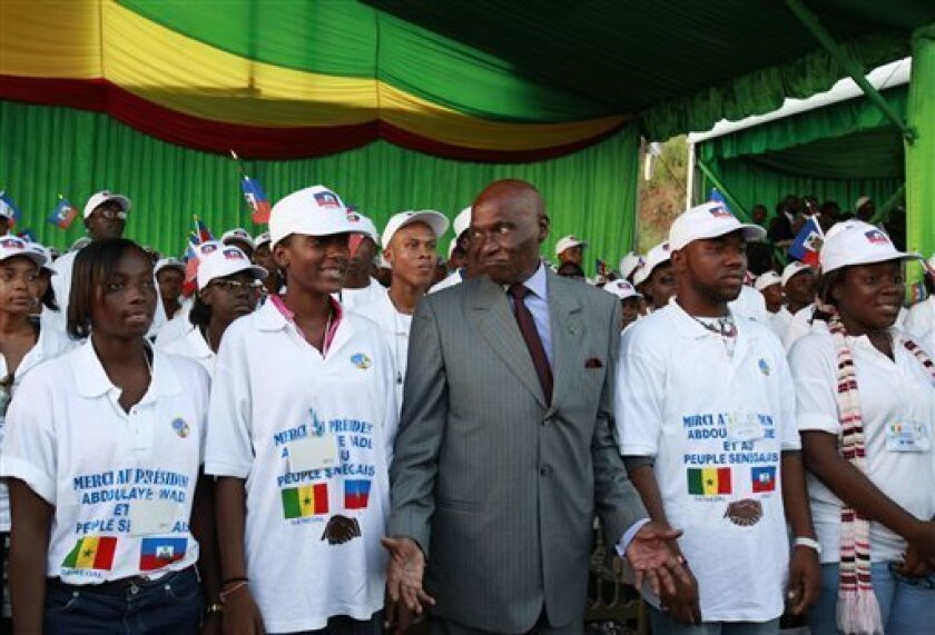 Senegalese President Abdoulaye Wade, center, gestures as he poses for a picture with Haitian students, wearing tee-shirts reading 'Thank you President Wade' at a ceremony welcoming the students to Dakar, Senegal Wednesday, Oct. 13, 2010. Senegal is one of the poorest countries in the world and its
