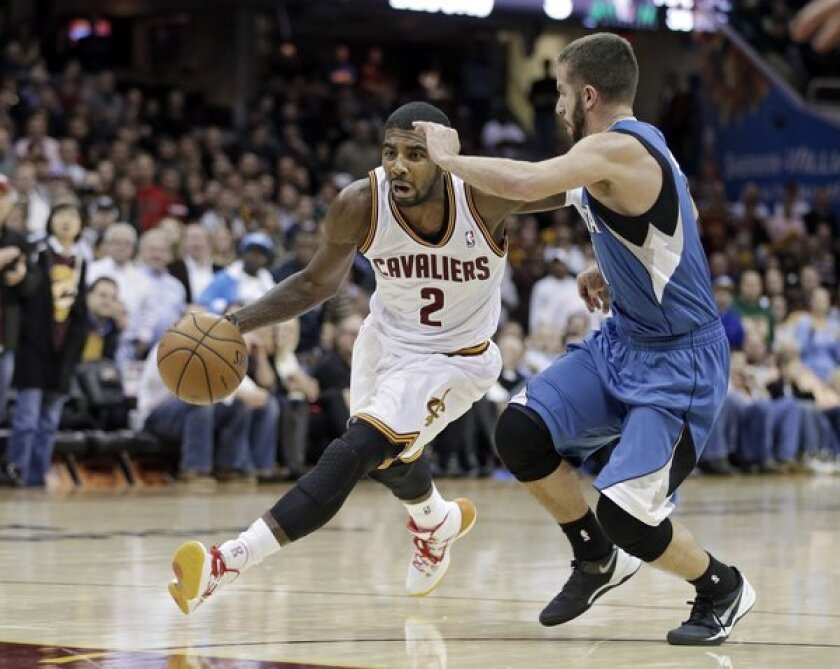 Cleveland's Kyrie Irving, left, drives past Minnesota's J.J. Barea during the Cavaliers' 93-92 win.